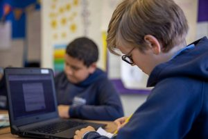 Computing lesson - student and laptop